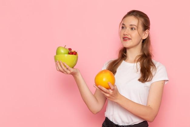 ピンクの壁に新鮮な果物とグレープフルーツとプレートを保持している白いtシャツの若い女性の正面図