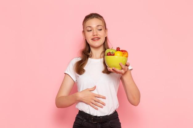淡いピンクの壁に新鮮な果物とプレートを保持している白いtシャツの若い女性の正面図