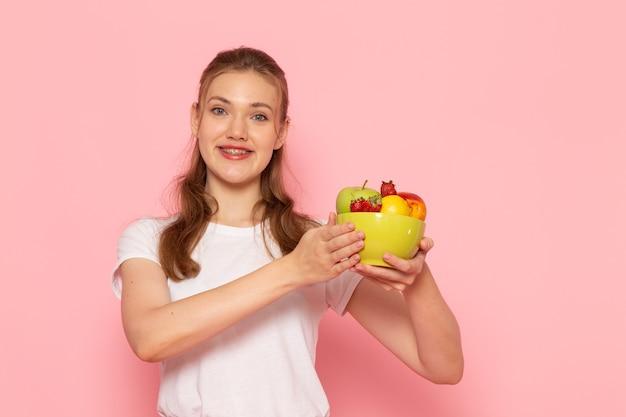 淡いピンクの壁に笑顔の新鮮な果物とプレートを保持している白いtシャツの若い女性の正面図