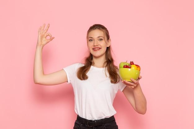 ピンクの壁に笑顔の新鮮な果物とプレートを保持している白いtシャツの若い女性の正面図