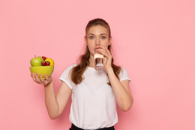 분홍색 벽에 과일과 물 마시는 유리 접시를 들고 흰색 티셔츠에 젊은 여성의 전면보기