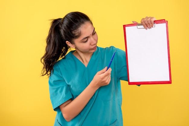 黄色の壁にクリップボードを見ている若い女性の正面図