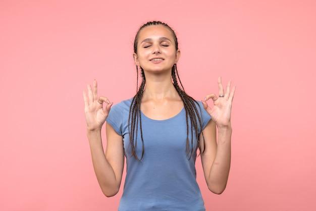 ピンクで瞑想する若い女性の正面図