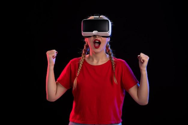 Вид спереди молодой женщины, играющей в виртуальную реальность на темной ультразвуковой визуальной игре