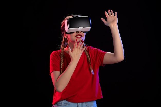 Вид спереди молодой женщины, играющей в виртуальную реальность на темной ультразвуковой игре