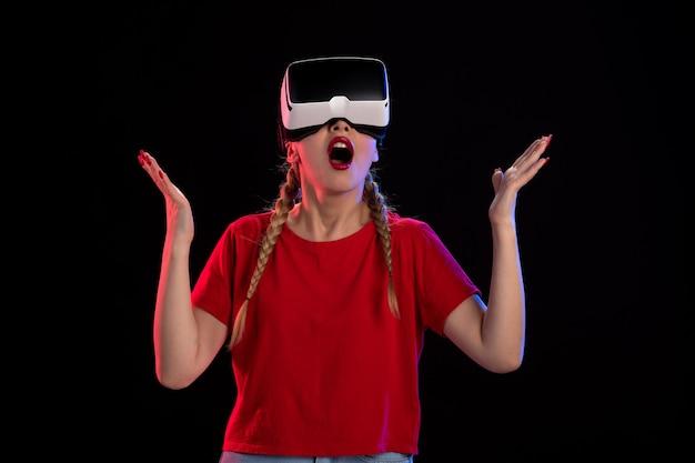 Вид спереди молодой женщины, играющей в виртуальной реальности на темной стене