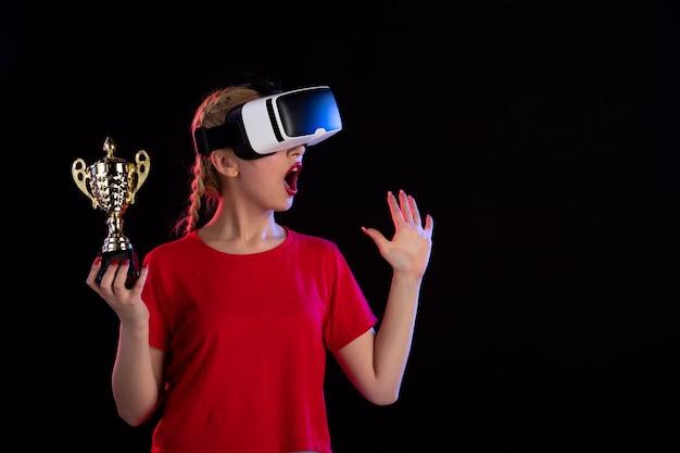 어두운 게임 기술 비주얼에 vr 및 우승 컵을 재생하는 젊은 여성의 전면보기