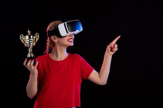 Вид спереди молодой женщины, играющей в vr и выигравшей кубок на темном игровом визуальном d