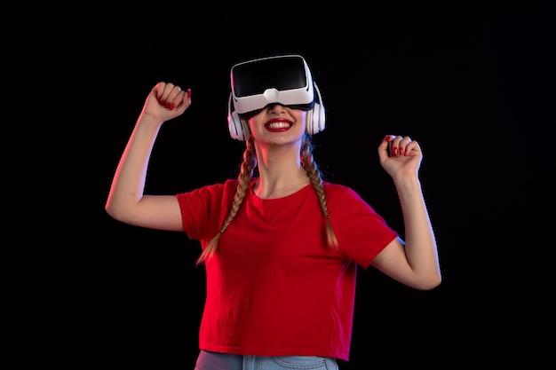 어두운 기술 게임 d에 헤드폰에서 vr을 재생하는 젊은 여성의 전면보기