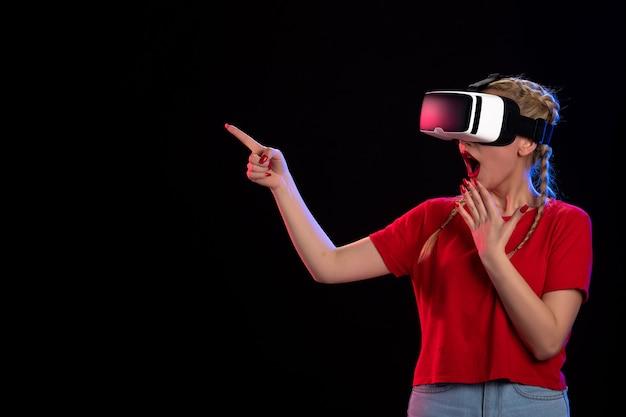 어두운 게임 기술 비주얼에 vr을 재생하는 젊은 여성의 전면보기