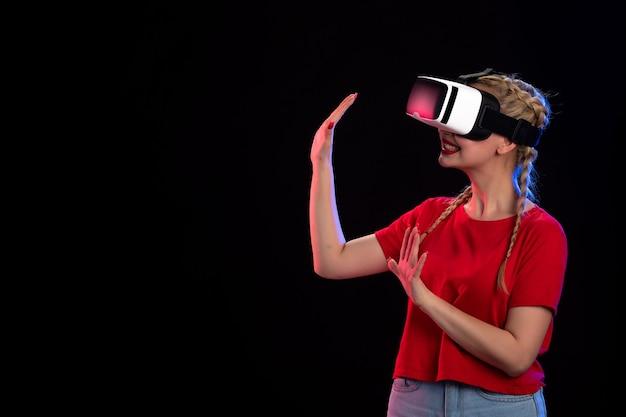 Вид спереди молодой женщины, играющей vr на темной стене