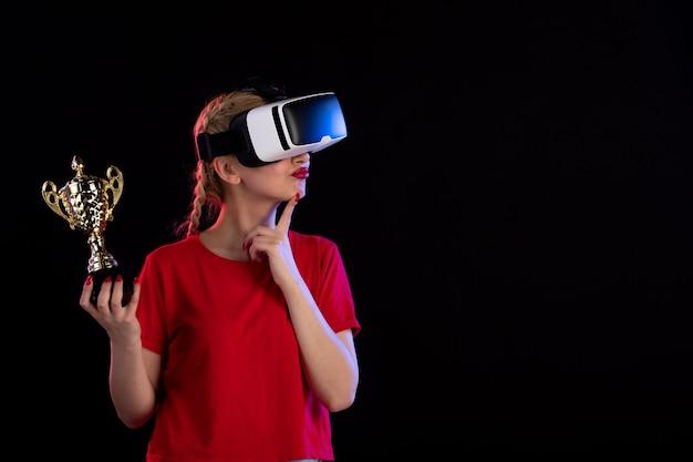 어두운 바닥 게임 비주얼 기술 d에 우승자 컵과 vr을 재생하는 젊은 여성의 전면보기