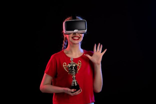 어두운 바닥 비주얼 d 기술 게임에 우승자 컵과 vr을 재생하는 젊은 여성의 전면보기