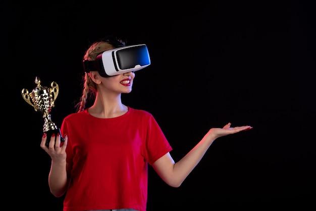 어두운 바닥 비주얼 기술 게임에서 우승자 컵과 함께 vr을 재생하는 젊은 여성의 전면보기
