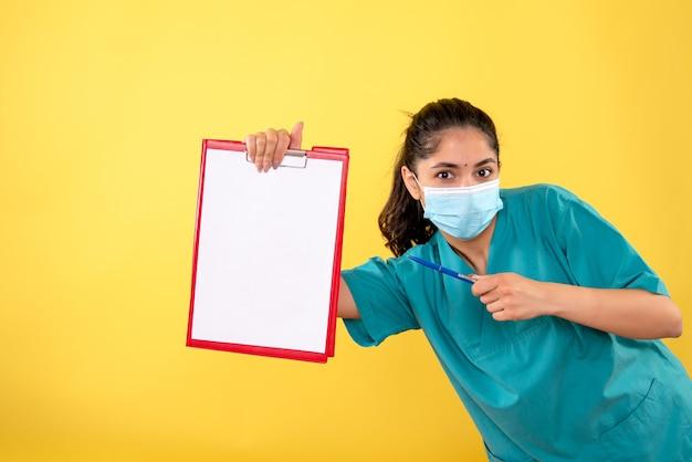 Вид спереди молодой женщины, указывая на буфер обмена, держа ручку на желтой стене