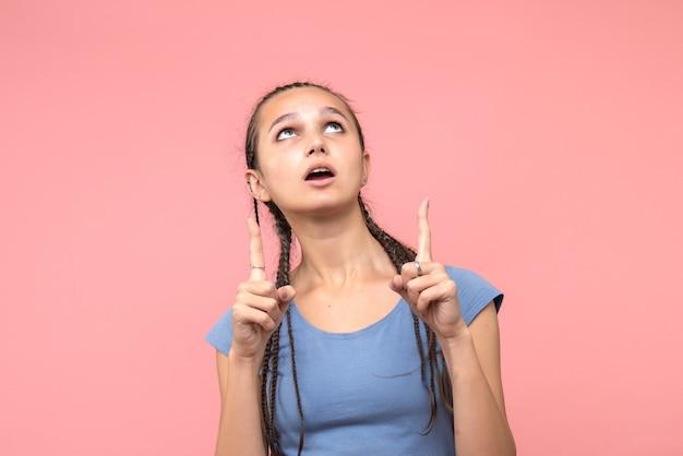 ピンクの空を指している若い女性の正面図 無料写真