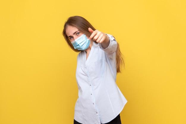 黄色の壁を指している若い女性の正面図