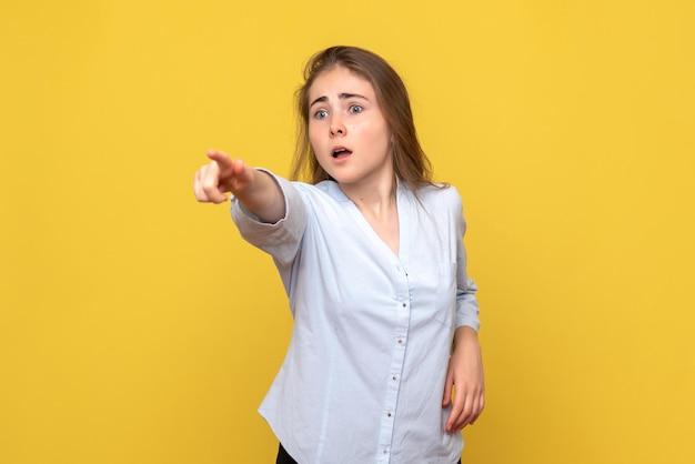 노란색 벽에 가리키는 젊은 여성의 전면보기