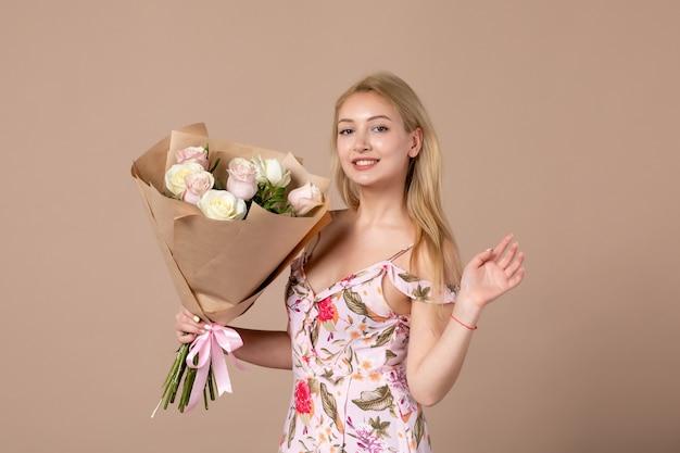 茶色の壁に美しいバラの花束とポーズをとって若い女性の正面図