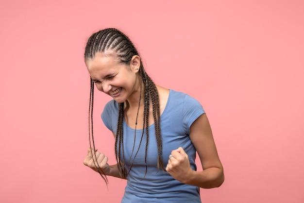 ピンクで喜んでいる若い女性の正面図