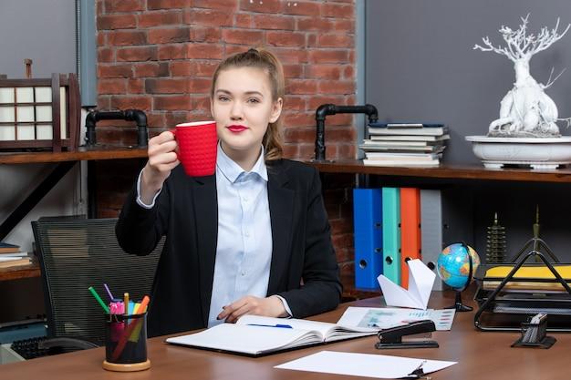 테이블에 앉아 사무실에서 카메라를 위해 포즈를 취하는 빨간 컵을 들고 있는 젊은 여성의 전면 모습