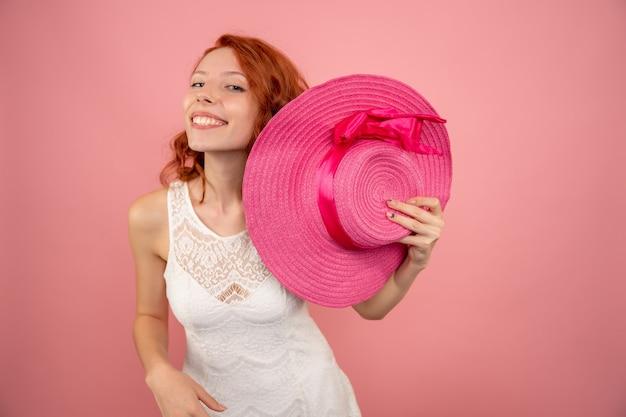 분홍색 벽에 웃 고 젊은 여성의 전면보기
