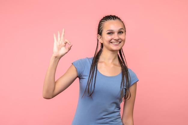 Вид спереди молодой женщины, улыбающейся на розовом
