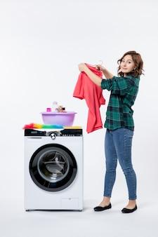 흰 벽에 있는 세탁기에서 깨끗한 옷을 꺼내는 젊은 여성의 전면
