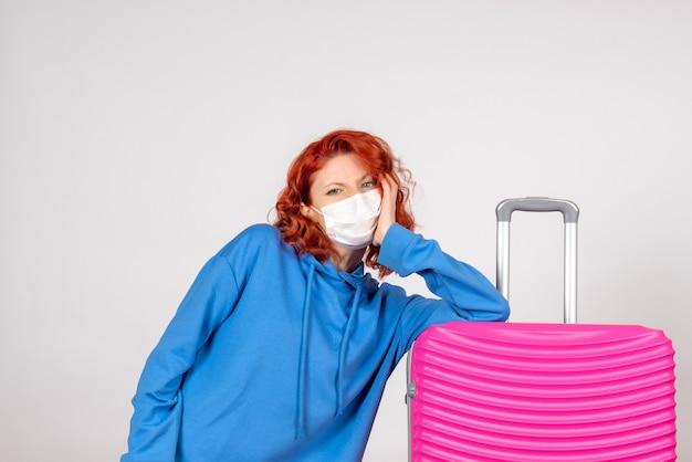 白い壁にマスクでピンクのバッグと若い女性観光客の正面図