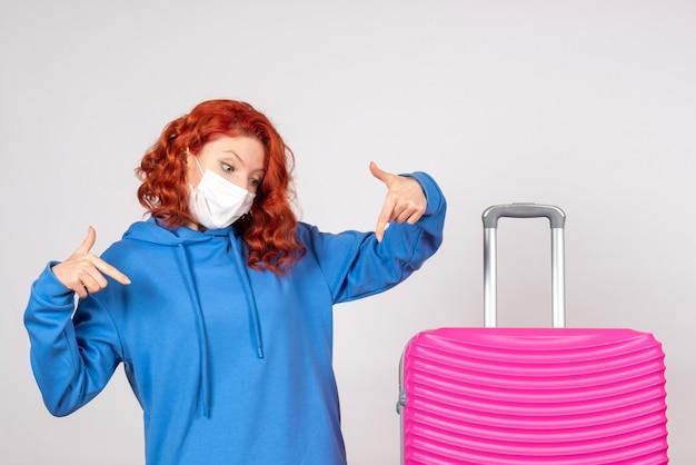 흰 벽에 마스크에 분홍색 가방을 가진 젊은 여성 관광객의 전면보기