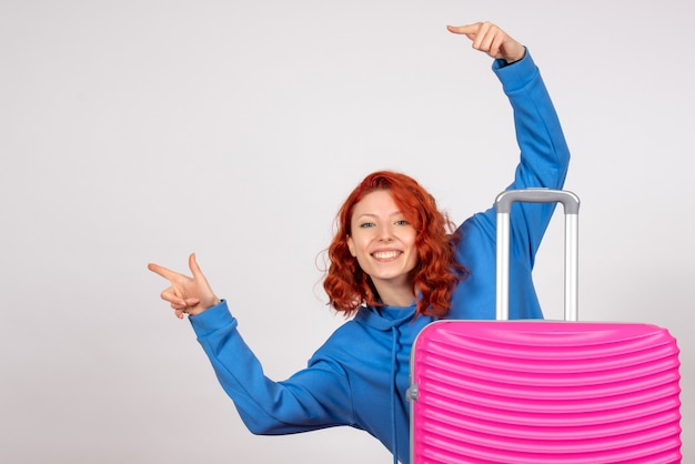 白い壁にピンクのバッグと若い女性観光客の正面図