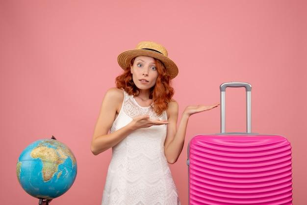 밝은 분홍색 벽에 분홍색 가방을 가진 젊은 여성 관광객의 전면보기