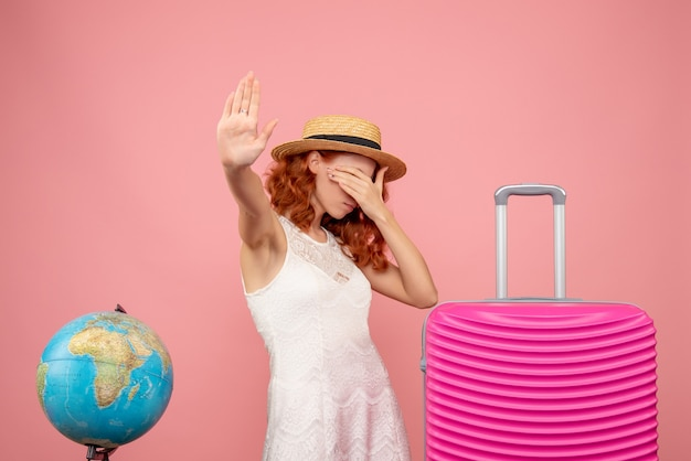 분홍색 벽에 분홍색 가방을 가진 젊은 여성 관광객의 전면보기