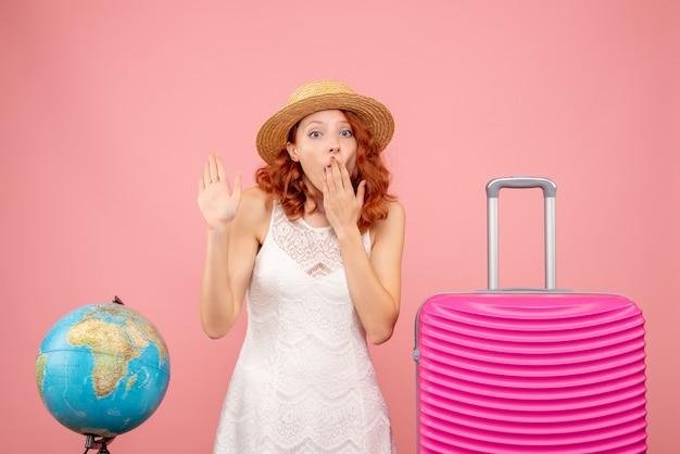 Вид спереди молодой туристки с розовой сумкой на розовой стене