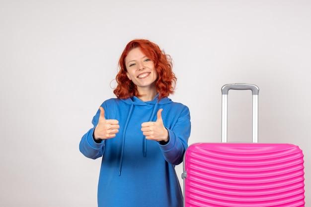흰 벽에 분홍색 가방을 가진 젊은 여성 관광객의 전면보기
