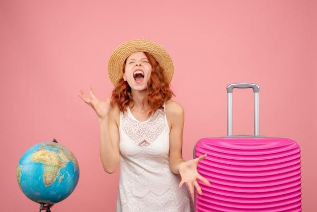 ピンクの壁にピンクのバッグが叫んでいる若い女性観光客の正面図