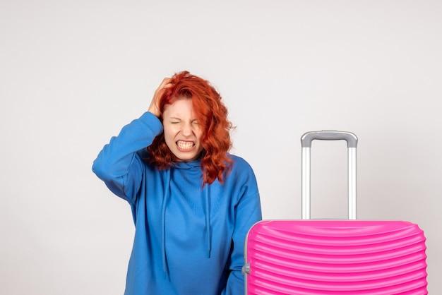 白い壁に頭痛に苦しんでいるピンクのバッグを持つ若い女性観光客の正面図