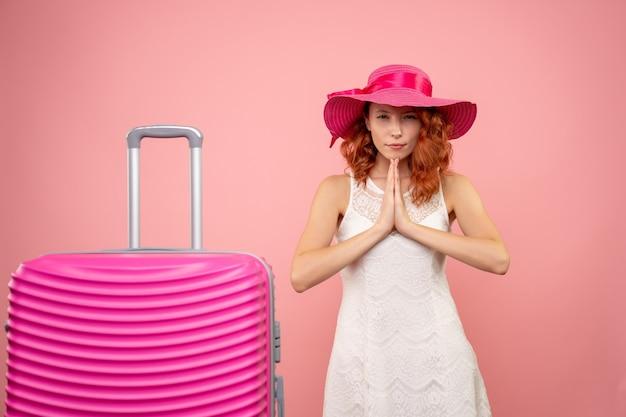 Вид спереди молодой туристки с розовой шляпой и сумкой на розовой стене