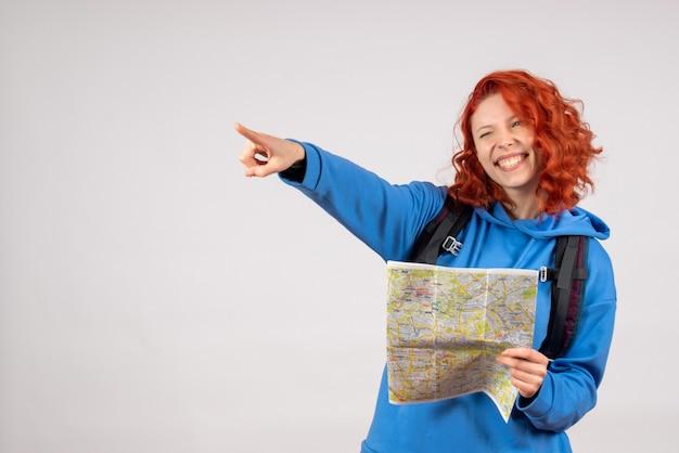 Вид спереди молодой женщины с рюкзаком и картой на белой стене