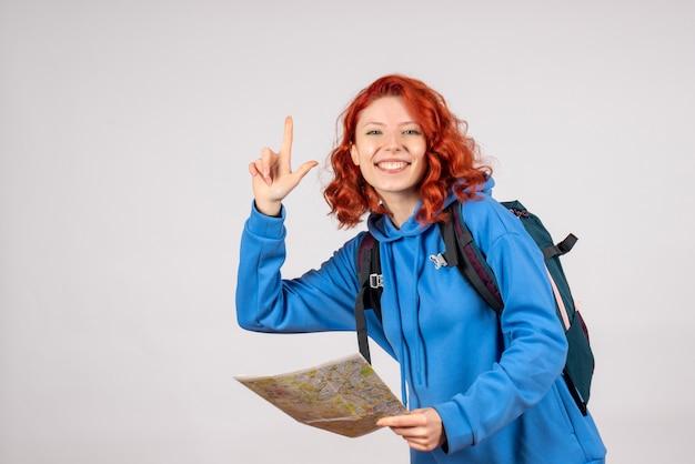 バックパックと白い壁の上の地図を持つ若い女性の正面図