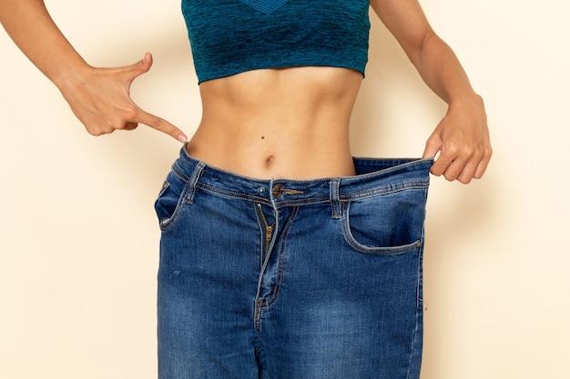 明るい白い壁に体重をチェックする青いシャツのフィットボディを持つ若い女性の正面図