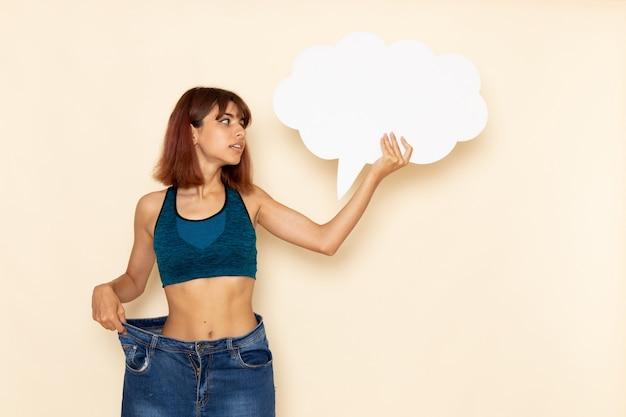 밝은 흰색 벽에 큰 흰색 기호를 들고 파란색 셔츠에 맞는 몸을 가진 젊은 여성의 전면보기