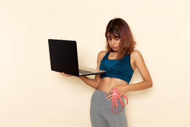 흰 벽에 그녀의 노트북을 들고 파란색 셔츠에 맞는 몸을 가진 젊은 여성의 전면보기