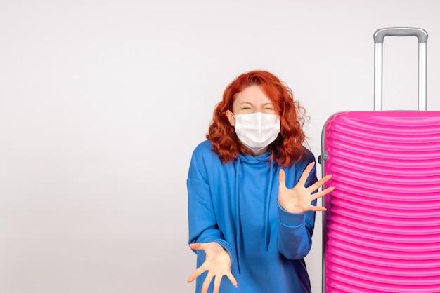 白い壁にマスクで彼女のピンクのバッグを持つ若い女性の正面図