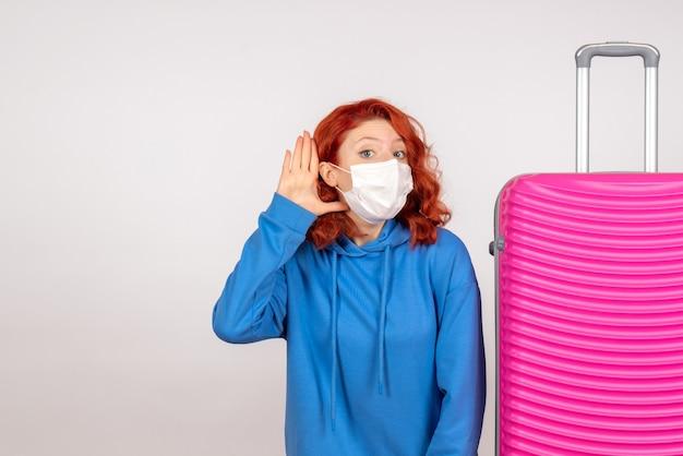 白い壁にピンクのバッグを持つ若い女性の正面図
