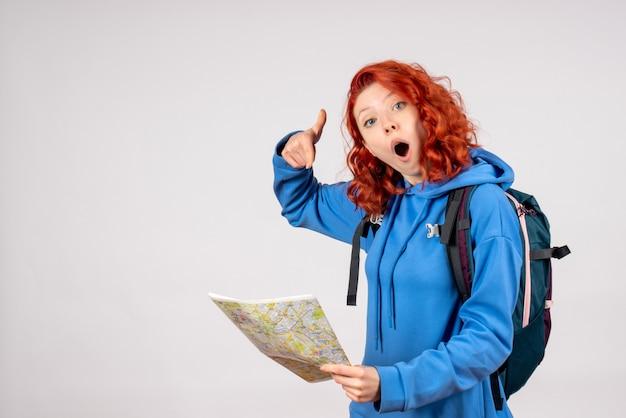 白い壁に地図と若い女性の正面図