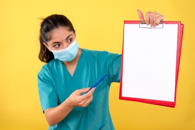 黄色の壁にクリップボードを保持しているマスクを持つ若い女性の正面図
