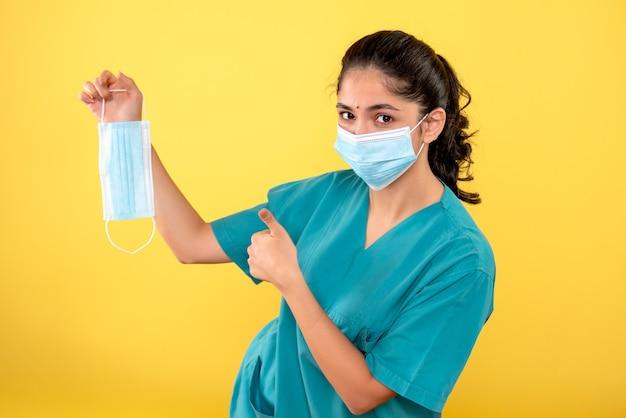 노란색 벽에 가입 엄지 손가락을 만드는 마스크를 들고 의료 마스크와 젊은 여성의 전면보기