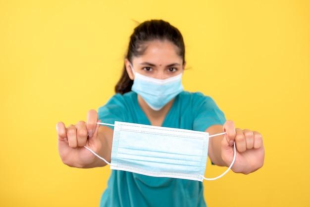 黄色の隔離された壁にマスクを保持している医療マスクを持つ若い女性の正面図