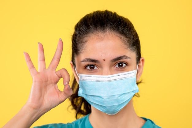 노란색 벽에 좋아요 기호를 만드는 의료 마스크와 젊은 여성의 전면보기